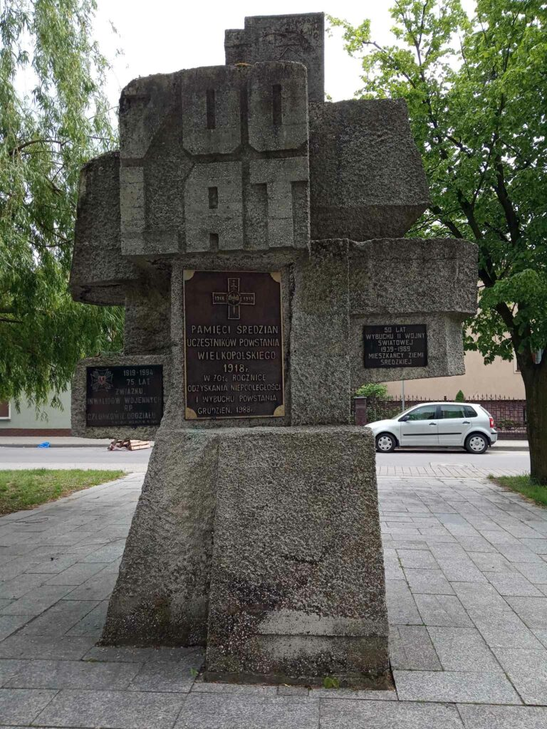 Pomnik 700-lecia miasta Środa Wielkopolska z metalową tablicą z podobizną krzyża powstańczego, poświęcona pamięci średzian uczestników Powstania Wielkopolskiego 1918 r.